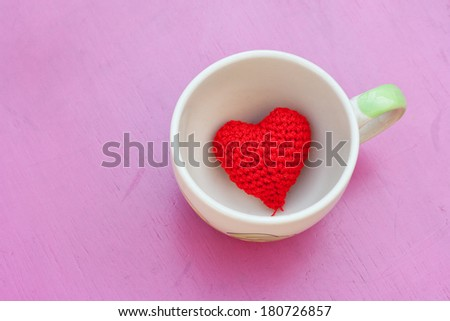 red heart in the coffee cup on pink table