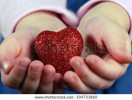 red heart in the hands of a child - stock photo