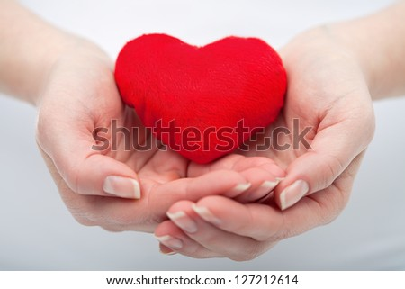 Red heart in the protective woman hand