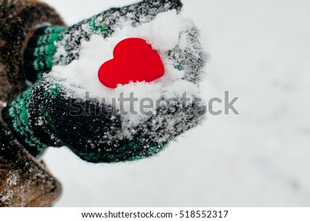 red heart in warm gloves