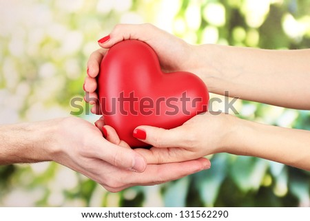 Red heart in woman and man hands, on green background - stock photo