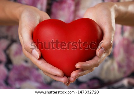 red heart in woman's hands, blurred lilac background - stock photo