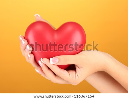 Red heart in woman's hands, on orange background close-up