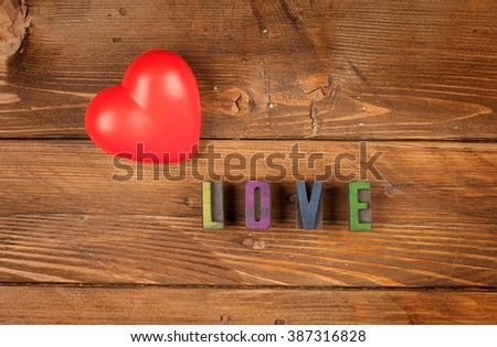 red heart  in wood background and word love in letterpress type - stock photo