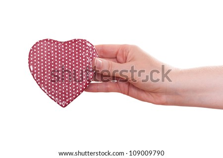 Red heart is holding from a female hand