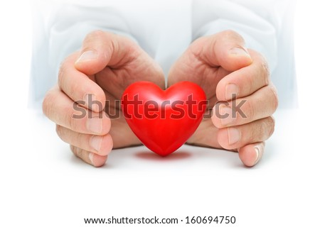 Red heart is protected by the human hands - stock photo
