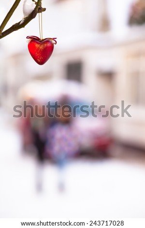 Red heart made of glass hanging on a twig in white winter christmas time at a small town street background with car and children/Winter Street Scene Background with Heart - stock photo