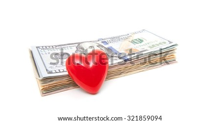 Red heart next to pile of dollar notes - stock photo