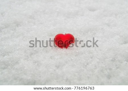 red heart on a background of pure white snow