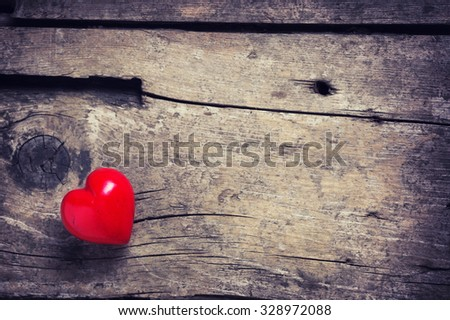 Red heart on aged wooden background. Selective focus. Place for text. Toned image. - stock photo