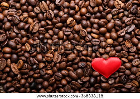 Red heart on coffee beans background - stock photo