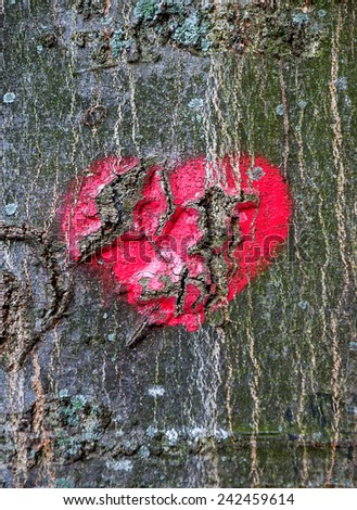Red heart on cracked mossy tree bark. Symbol of true love - in sickness and in health, in good times and in bad, and in joy as well as in sorrow. Broken heart idea. - stock photo
