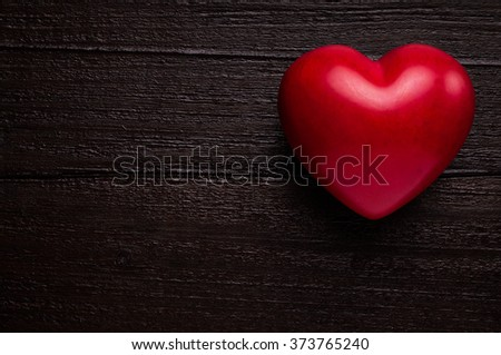 Red heart on dark wooden background - stock photo
