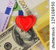 Red heart on european and american money - stock photo