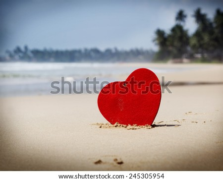 Red heart on exotic sandy beach - Love concept - stock photo