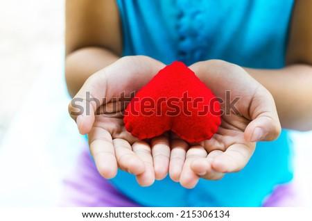 red heart on hand little girl - stock photo
