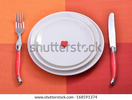 Red heart on plate with fork and knife