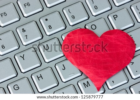Red heart on the computer keyboard. Internet dating concept