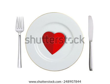 red heart on white plate, spoon and fork isolated on white