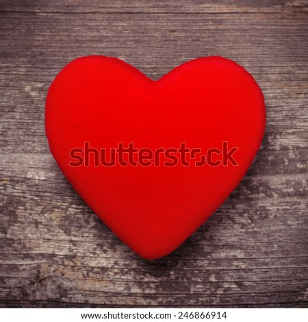 Red heart on wood table close-up - stock photo