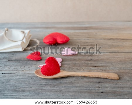 Red heart on wooden ladle,