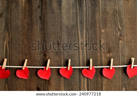 Red heart paper cut out with clothes pins.Image of Valentines day season. - stock photo