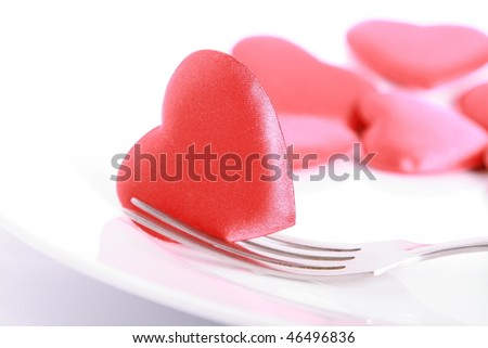 Red heart pierced by fork on the plate - stock photo