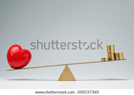 Red heart shape and money coins stack balancing on a seesaw - stock photo