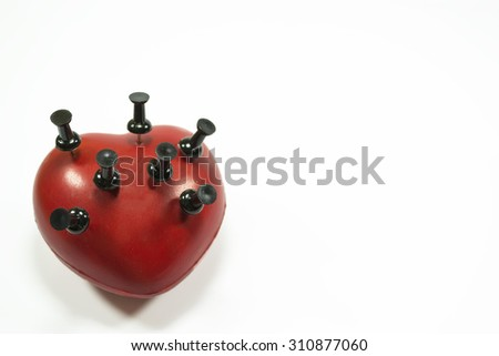 Red heart shape with black push pins puncturing it , conceptual image about heart related medical illnesses , isolated on white background - stock photo
