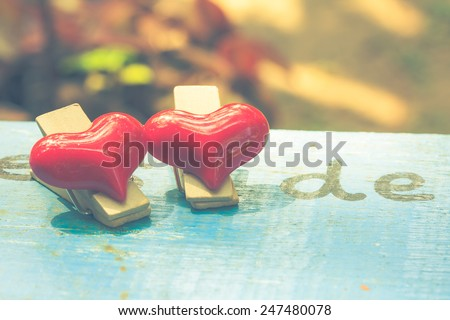 red heart shape wood clip on old table vintage color tone - stock photo
