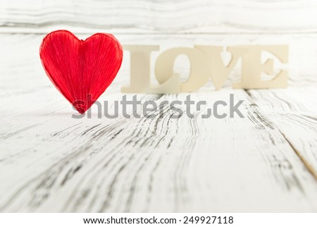 Red heart shaped and in the background wooden letters forming word love. Valentines Day background - stock photo