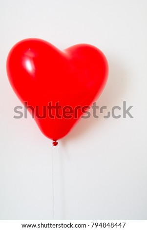 Red heart shaped balloon on a string isolated on white