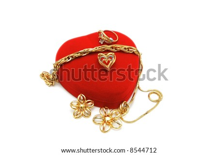Red heart-shaped box and gold jewelery on white - stock photo