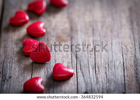 Red heart shaped candies on a rustic wooden surface