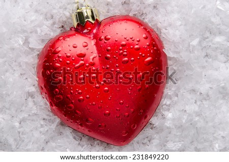 Red heart shaped Christmas decorations on snow. - stock photo