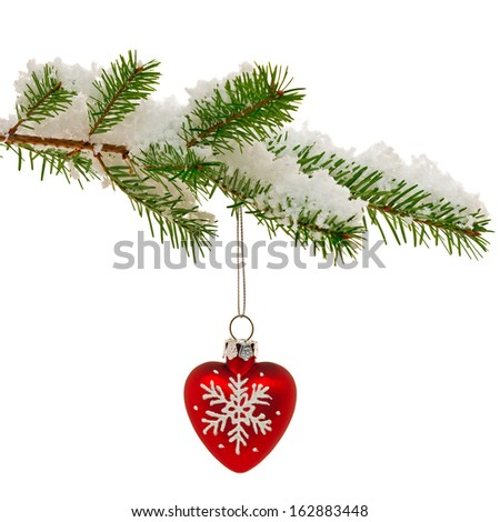 Red heart shaped Christmas ornament hanging from the branch of a Christmas tree covered in snow, isolated on a white background. - stock photo