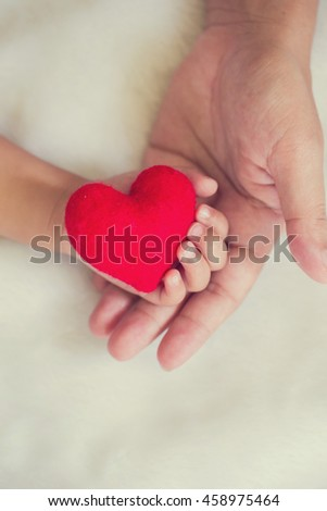 Red heart shaped in mom's hand to baby hand on white soft blanket background