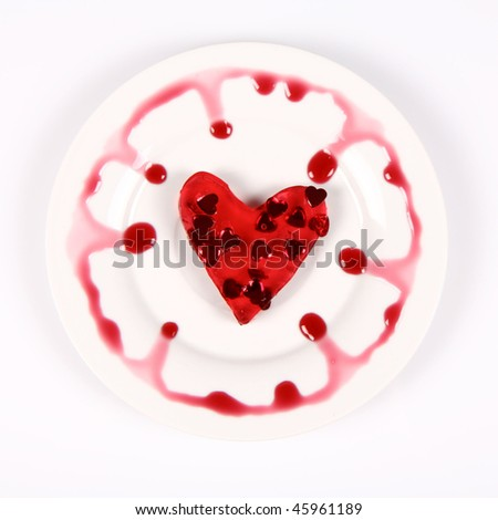 Red heart shaped jello filled with heart shaped confetti on a plate decorated with fruity custard - stock photo