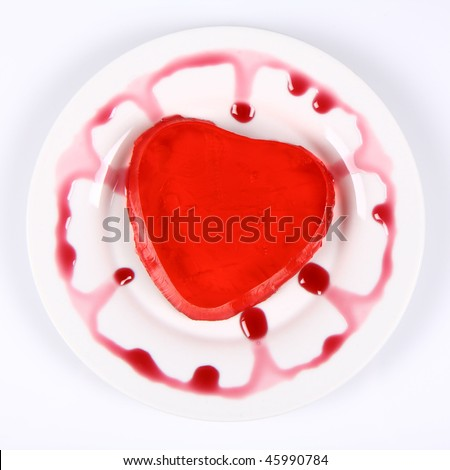 Red heart shaped jello on a plate decorated with fruity custard - stock photo