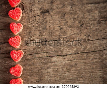 Red heart shaped jelly sweets on a vintage wooden background. Top view.