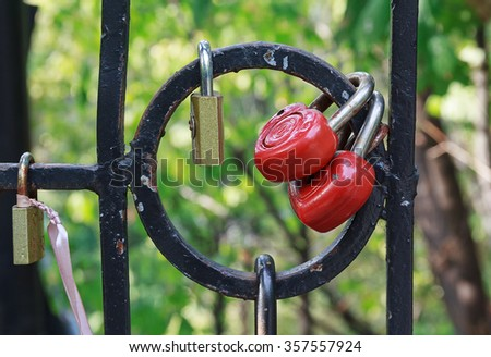 Red heart-shaped locks are hanging on the bridge lovers - stock photo