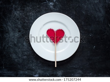 Red heart shaped lollipop and white plate on black chalkboard background. Valentines day meal concept.
