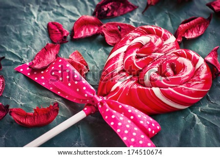 Red heart-shaped lollipop of valentines day on texture background/  Valentines day background
