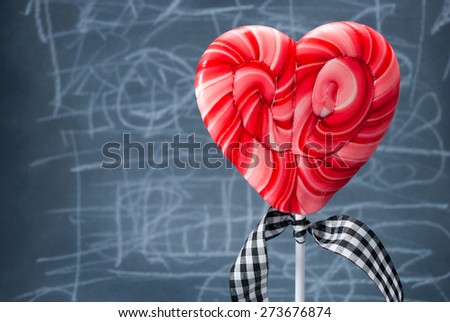 Red heart-shaped lollipop over scribble background.