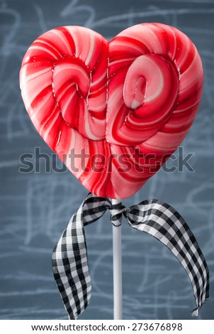 Red heart-shaped lollipop over scribble background. - stock photo