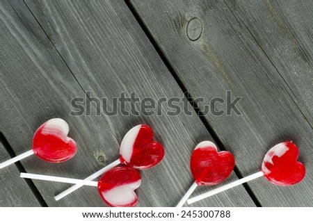 Red heart-shaped lollipops on wooden surface with free space - stock photo
