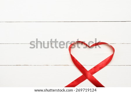 Red heart shaped ribbon over white wooden background with copy space - stock photo