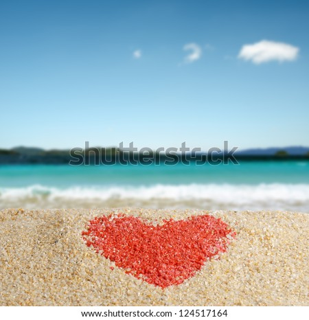 Red heart sign in yellow sand. - stock photo
