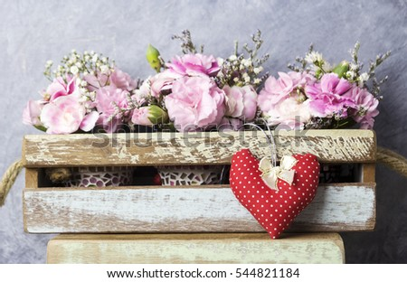 Red heart with bow and pink carnation flowers in wood box