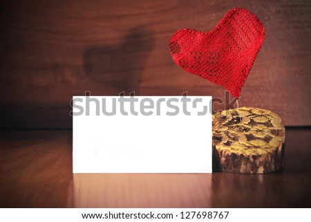 Red heart with card on wood background. Love greeting card